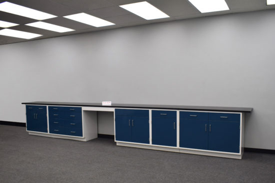 Blue laboratory cabinets with black epoxy work surface and desk.