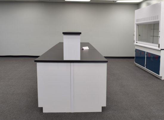 Laboratory island with desk area and center shelf.
