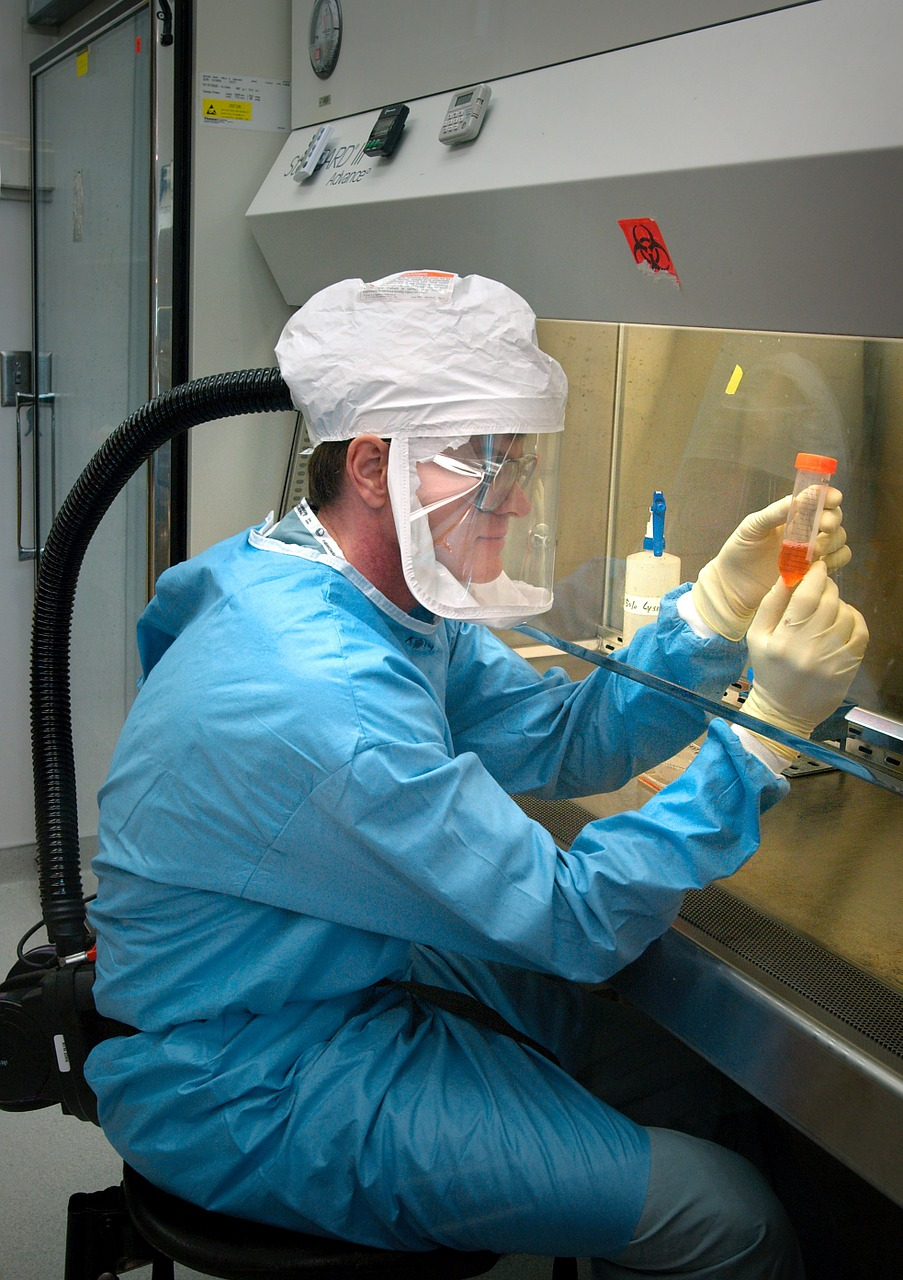 Microbiologist working in a fume hood.