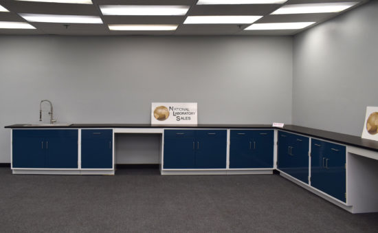 Blue laboratory cabinets with black countertops and two desks.